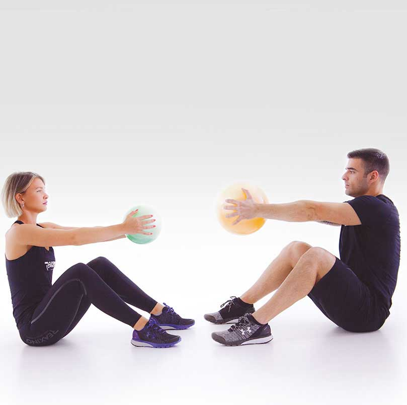 athletes training couple exercises on floor with fluiball